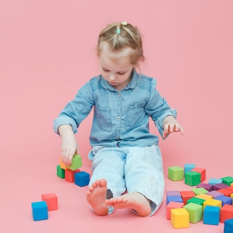 A charming little girl in denim clothes on a pink background plays with wooden colored cubes.