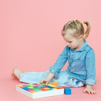 A charming little girl in denim clothes on a pink background puts wooden multi-coloured cubes in a white box.