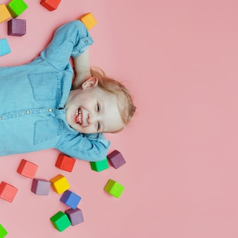 A charming little girl in denim clothes with wooden colored cubes and laughing
