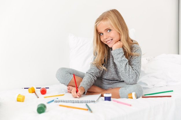 Charming little girl drawing with pencils on white bed