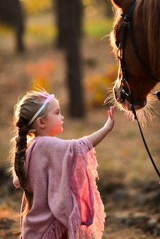Charming little girl dressed like a princess stands with a horse in the autumn forest