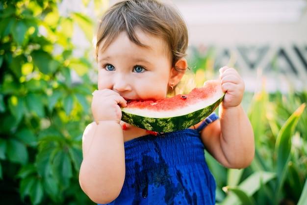 매우 귀여운 식물의 배경에 마당에서 수박을 먹는 매력적인 어린 소녀