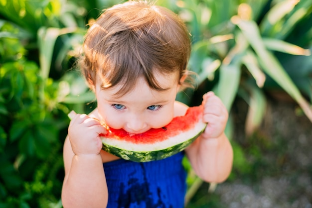 Charming little girl eating watermelon in the yard on the background of plants, very cute
