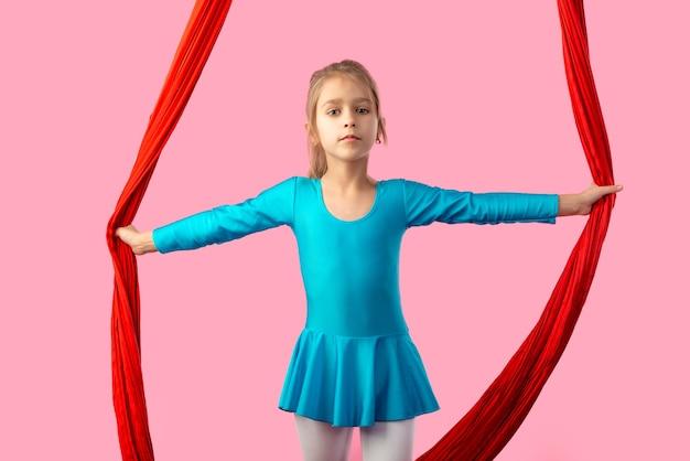 빨간색 바람이 잘 통하는 리본으로 성능을 위해 준비된 파란색 체조 정장에 매력적인 어린 소녀