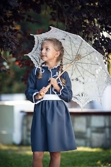 화창한 여름 날에 도시에서 걷는 복고풍 드레스에 매력적인 어린 소녀. 어린 소녀는 교복을 입는다.
