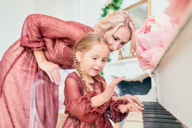 エレガントなドレスを着た魅力的な少女は、幸せな母親の隣でピアノを弾きます