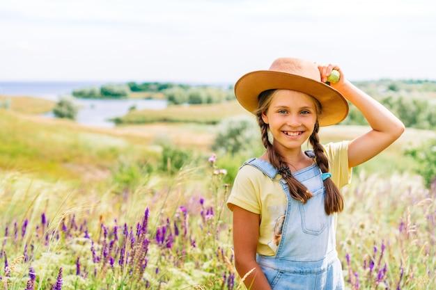 絵のような丘陵の風景に対してリンゴを手で押し帽子の魅力的な少女