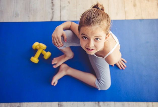 Charming little girl is sitting on yoga mat
