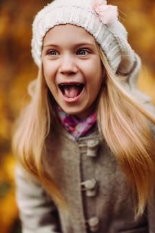 魅力的な小さな女の子が笑う-幸せな女の子。魅力的な秋。
