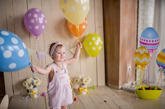 Charming little girl looks happy playing with colorful balloons