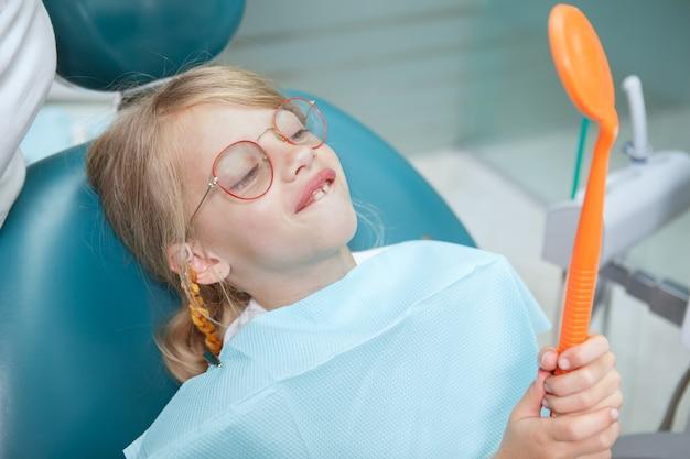歯科医院の鏡を見て、変な顔をしている魅力的な少女