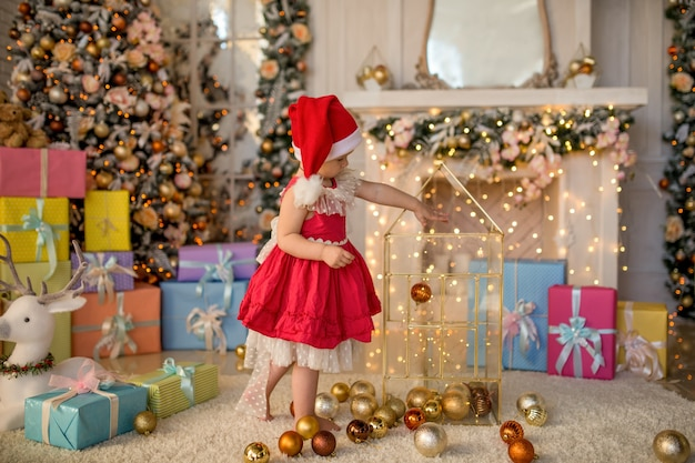 Charming little girl plays with christmas tree toys