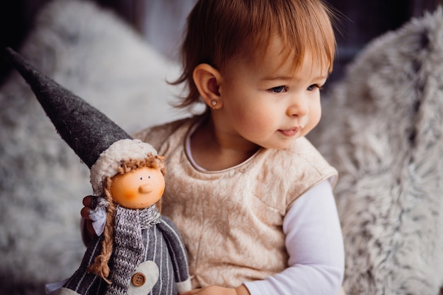 Charming little girl plays with a doll