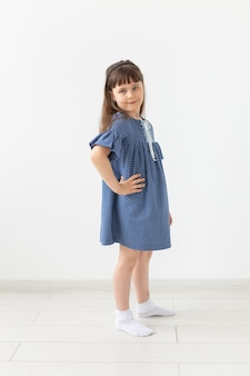 Очаровательная маленькая девочка позирует в синем платье в горошек на белом фоне. концепция классики