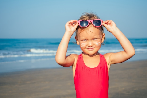 Charming little girl puts on sunglasses on the beach.