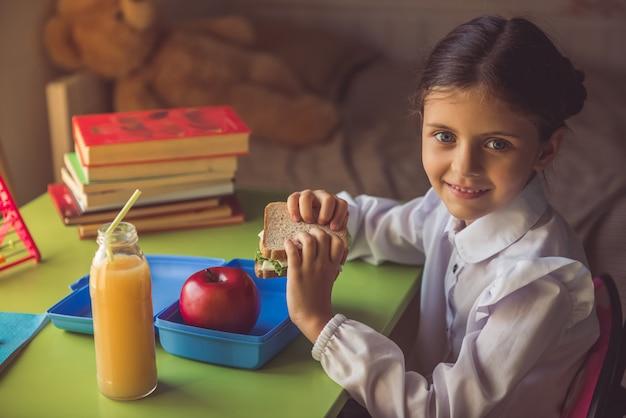 Charming little girl in school uniform is holding a sandwich
