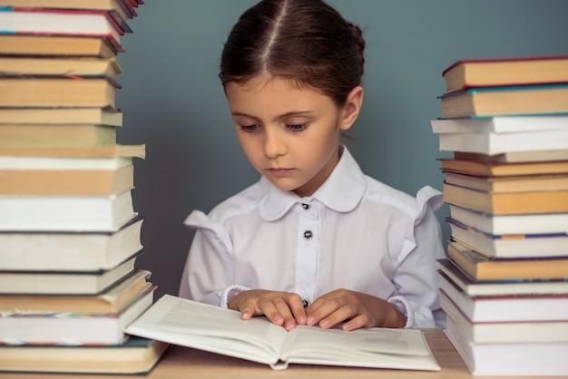 Charming little girl in school uniform is reading a book