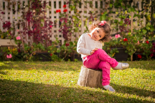 Charming little girl sitted on backyard in pink pants
