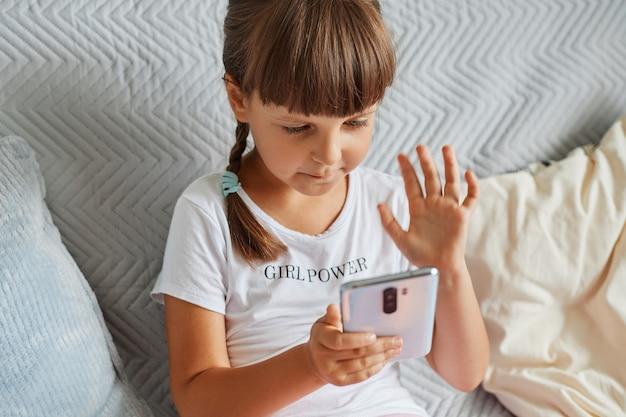 Очаровательная маленькая девочка сидит на диване с мобильным телефоном и проводит видеозвонок с друзьями, смотрит на экран устройства и машет рукой на камеру гаджета, ребенок в повседневной одежде.