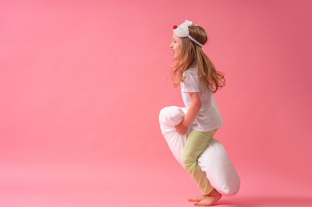 Charming little girl in a sleep mask and pajamas jumps and flies on pillows