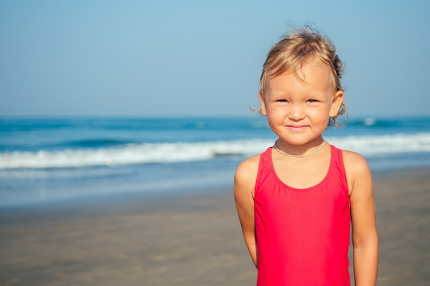 Charming little girl smiling and sunbathing on the beach