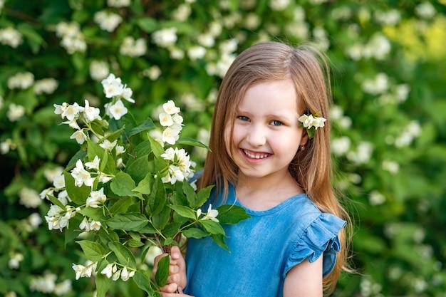 Очаровательная маленькая девочка нюхает цветы жасмина