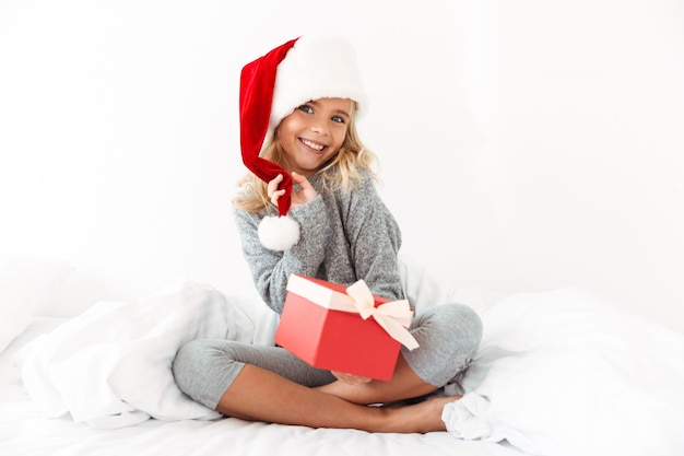 Charming little girl touching her santa's hat holding gift box,  while sitting on bed