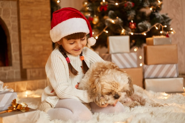 Charming little girl wearing white sweater and santa claus hat, playing with her puppy while sitting on floor near christmas tree, present boxes and fireplace.