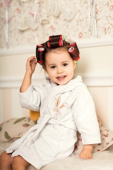 Charming little girl with curly hair using curlers