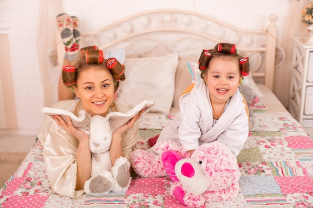A charming little girl with her mother in hair curlers are having fun. women's day. girl having fun with mom.
