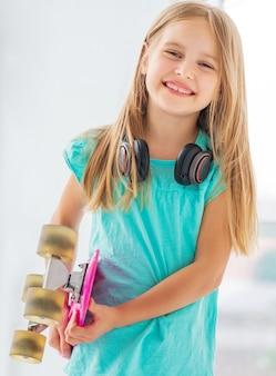 ペニーボードとヘッドフォンを持つ魅力的な少女