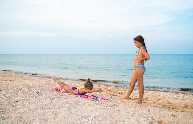 魅力的な小さな女の子は、晴れた暖かい夏の日にビーチでリラックスしながら体操をします。夏のスポーツとアクティブゲームのコンセプト。コピースペース