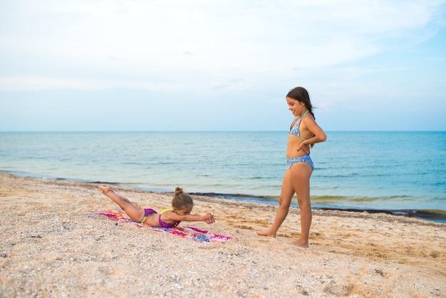 Очаровательные маленькие девочки делают гимнастические упражнения во время отдыха на пляже
