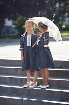 Очаровательные маленькие девочки в ретро платье гуляют по городу в солнечный летний день. у девушек истинный вкус к прекрасному. счастливые дети в униформе улыбаются на открытом воздухе.