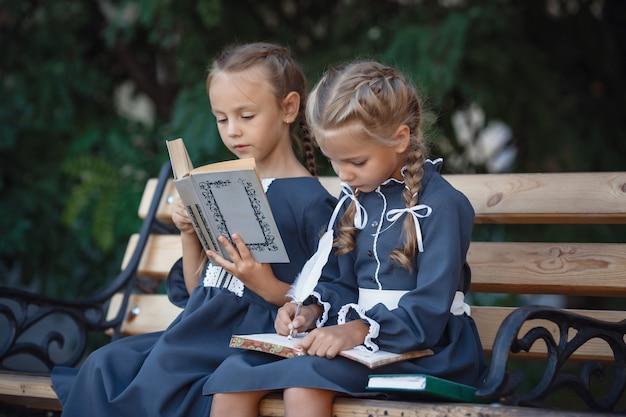 Очаровательные маленькие девочки в ретро платье гуляют по городу в солнечный летний день.