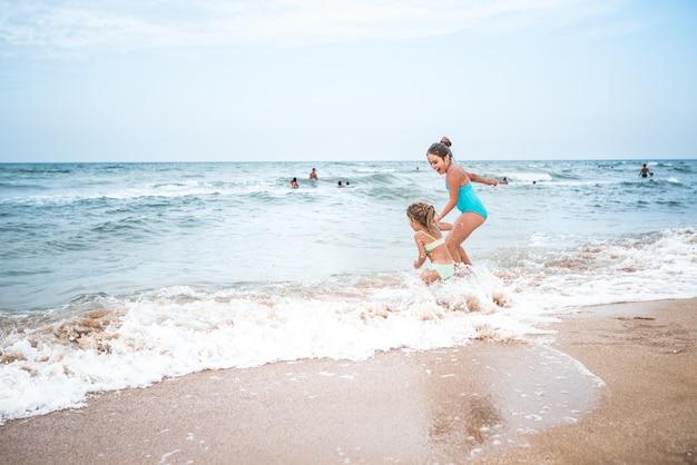 휴가 기간 동안 햇볕이 잘 드는 더운 여름날 바다의 파도에서 수영하고 튀는 매력적인 어린 소녀 자매