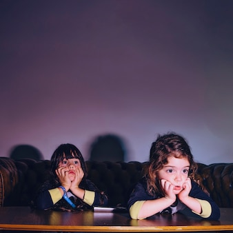 Charming little girls watching movie