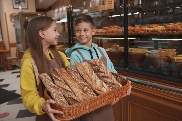 Charming little kids bakers selling delicious bread at their family bakery cafe