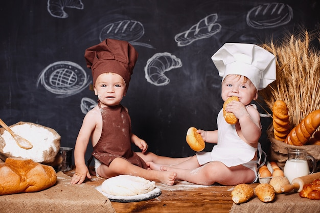 Charming little toddlers in aprons on table with bread