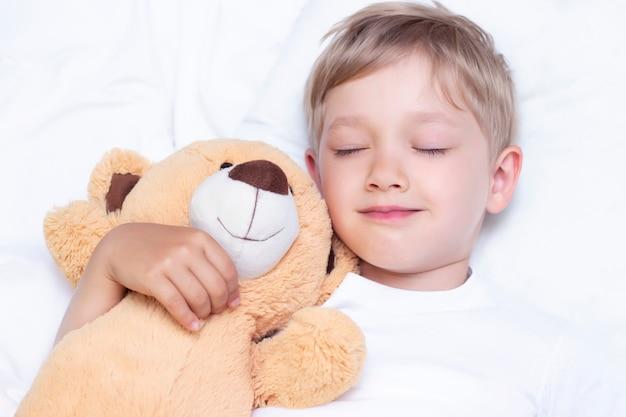 Очаровательный маленький белый мальчик спит в постели. обнимает мягкую игрушку