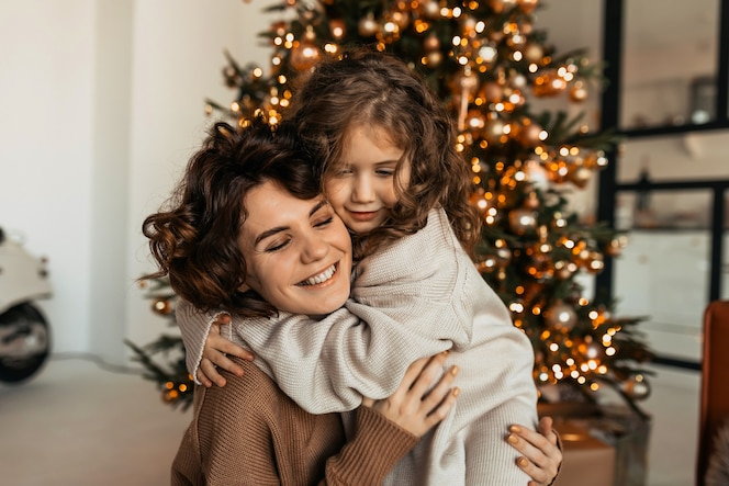 Charming lovable caucasian woman with curves hugging with her little daughter and celebrating christmas and new year
