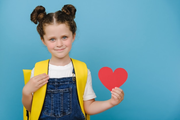 Charming lovely cute schoolgirl with yellow backpack holding hand red paper heart, happy looking at camera, posing isolated over blue studio background wall. people emotions and back to school concept