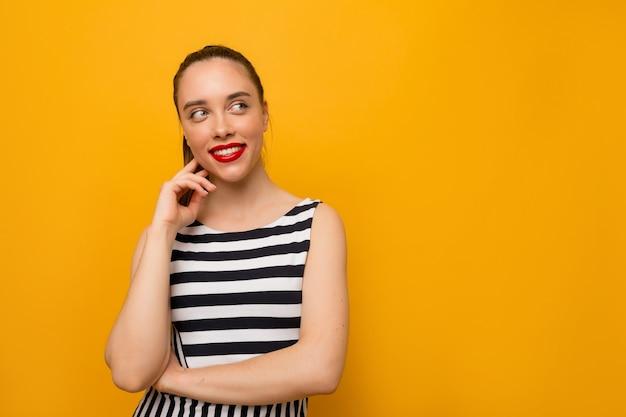 黄色に見上げて微笑んでストリップドレスを着て赤い唇を持つ魅力的な素敵な女の子