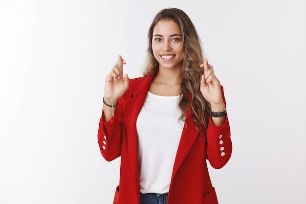 매력적인 운이 좋은 귀여운 여성은 취업 면접에 합격하기를 희망하며 행운을 위해 손가락을 교차하고 희망을 갖고 웃는 카메라가 자기 확신에 찬 결과를 기대하는 꿈을 꾸며 기도합니다, 흰 벽