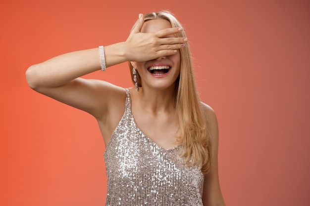 魅力的な幸運な発信ブロンドの誕生日の女の子は、見事なシルバーのきらびやかなドレスを着て友達を集めるパーティーナイトクラブを祝います