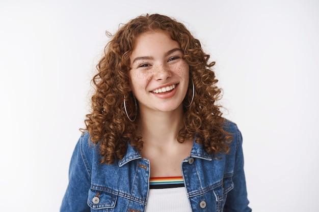 魅力的なラッキークィアヨーロッパの女の子生姜縮れ毛のそばかすのにきび化粧なしで広く笑って欠陥を受け入れることを楽しんでいる自己愛のボディポジティブ感情の概念、立っている白い壁