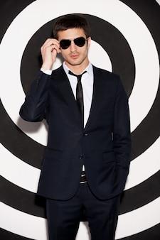 魅力的なマッチョ。黒と白の背景に立っている間彼のサングラスを調整するフルスーツのハンサムな若い男