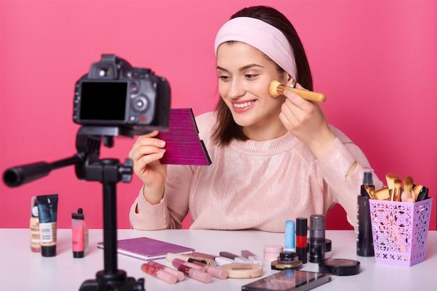 Очаровательный визажист наносит пудру косметической кисточкой, смотрит в зеркало, окружен множеством косметических средств, сидит перед камерой