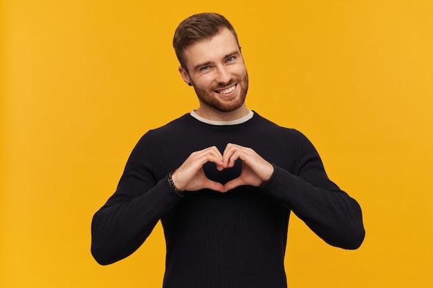 Очаровательный мужчина, красивый парень с волосами брюнетки и бородой. имеет пирсинг. в черном свитере. наклоняет голову и показывает знак сердца. изолированные над желтой стеной