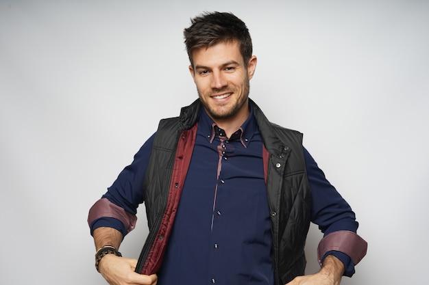広い笑顔と白い壁に分離された巻き上げられた袖を持つ魅力的な男性